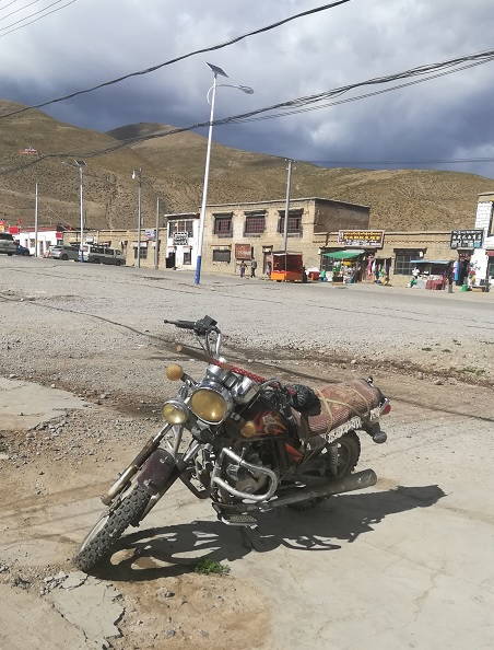 Motorcycle, decorated with talismans on the streets of Darchen